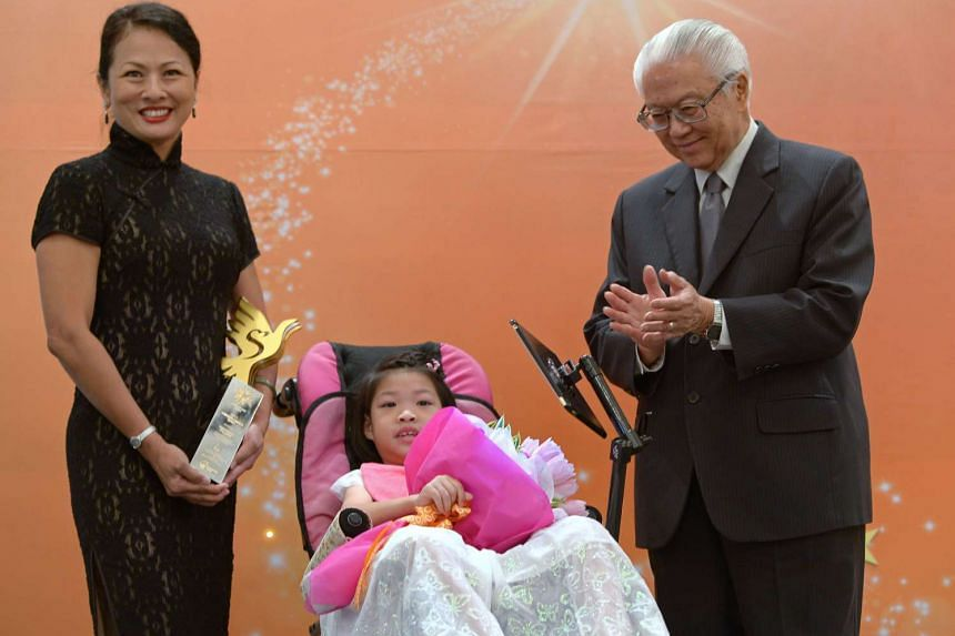 Ms Nicolette Rappa (left), UOB's Head of Group Strategic Communications and Customer Advocacy, with the company's Pinnacle Award presented by President Tony Tan (right). Fong Ruo En (centre), seven, a client of the Society for the Physically Disabled