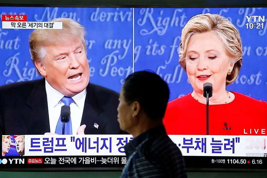 A man walks past a TV broadcast of the first presidential debate in Seoul, South Korea, Sept 27, 2016.