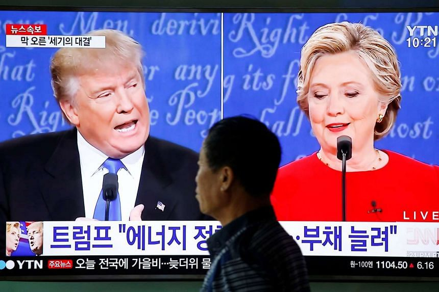 A man walks past a TV broadcast of the first US presidential debate in Seoul, South Korea, Sept 27, 2016.