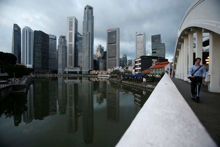 A man passes the skyline of the Central Business District on a portable scooter in Singapore.