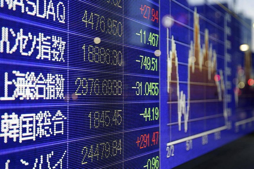 The Shanghai Stock Exchange Composite Index, centre, is displayed on an electronic stock board outside a securities firm in Tokyo.