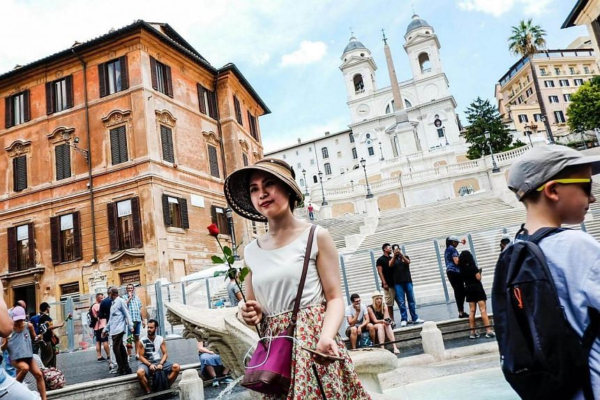 A tourist holding a rose in front of the Spanish Steps in Rome.