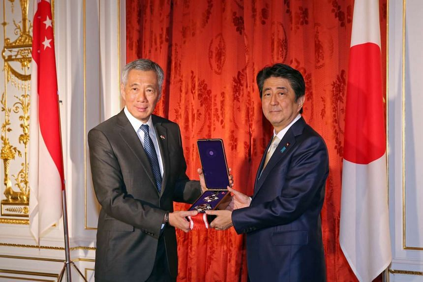 Prime Minister Lee Hsien Loong receives the Grand Cordon of the Order of Paulownia Flowers for the late Mr Lee Kuan Yew, from Japan PM Shinzo Abe.