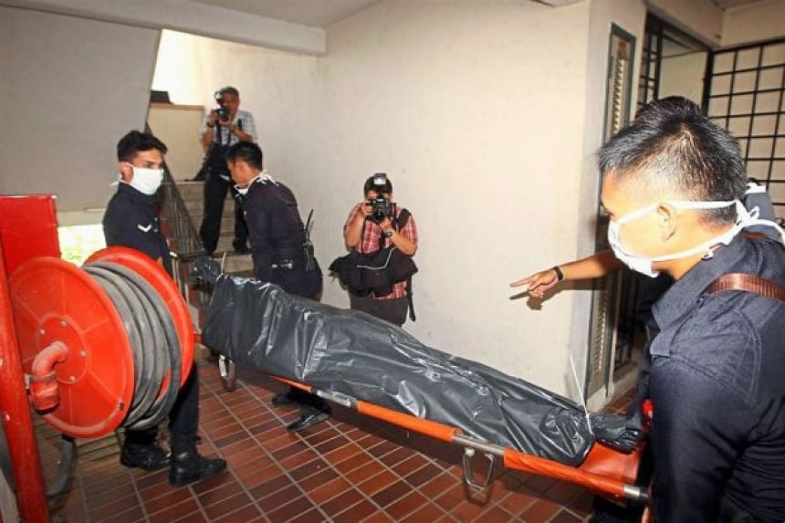 Police officers carrying Cheah's body out of the apartment in Taman Sri Sinar, Segambut.