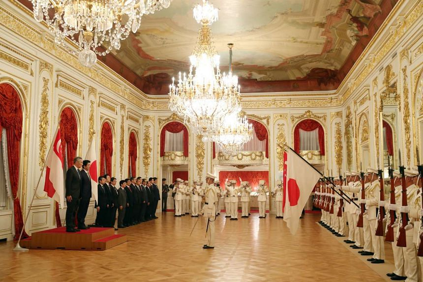 Prime Minister Lee Hsien Loong and Japan PM Shinzo Abe stand as the National Anthem of both countries are played at the Akasaka State Guest House.