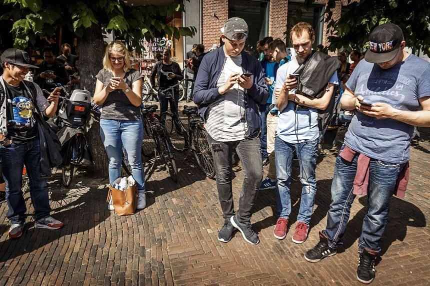 Gamers play with the Pokemon Go application on their mobile phone, at the Grote Markt in Haarlem, the Netherlands on July 13, 2016.