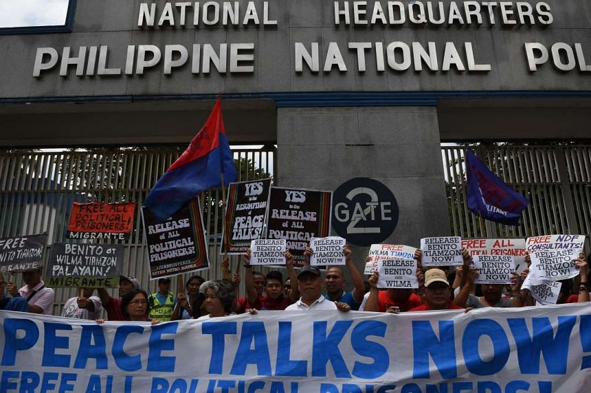 Activists and suppporters of communist rebel leaders hold a rally outside the gates of the police headquarters in Manila on Aug 19, 2016.