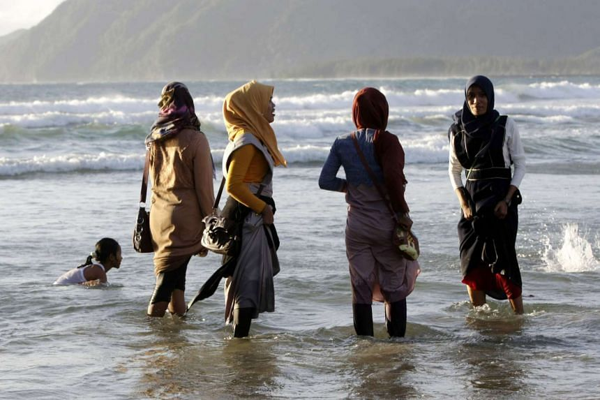 A group of local Muslim tourists in the water at the beach in Ule Lhuee, in Banda Aceh, Indonesia on Sept 14, 2016.