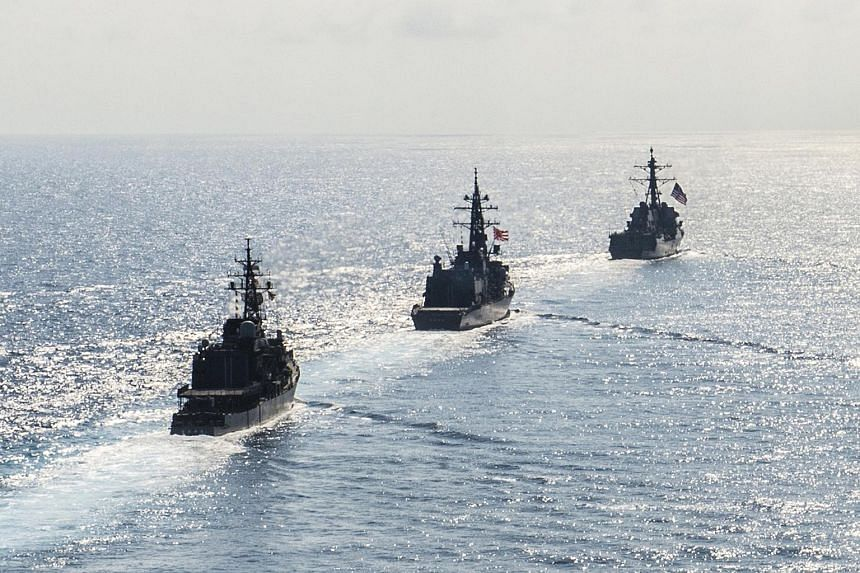 Arleigh Burke-class guided-missile destroyer USS Mustin transits in formation with Japan Maritime Self-Defense Force ships during bilateral training in South China Sea in 2015.