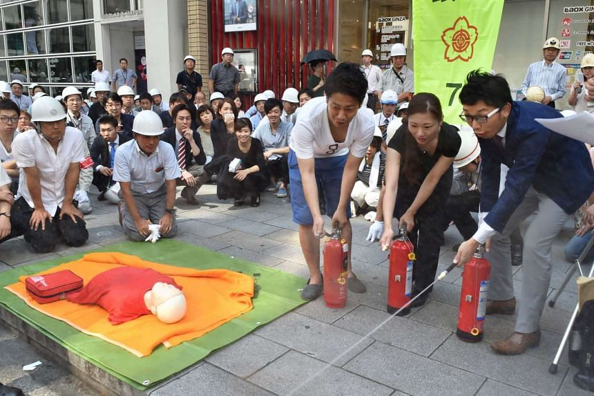 People learn how to use a fire extinguisher on the street during an annual disaster drill in the Tokyo's Ginza shopping and business district on Aug 26, 2016.