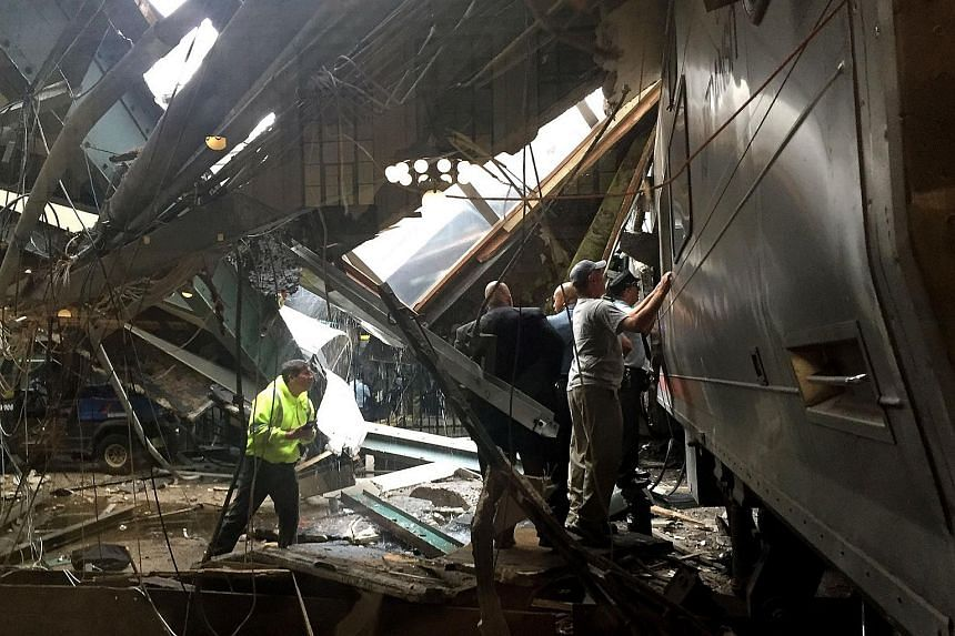 Train personel survey the NJ Transit train that crashed in to the platform at the Hoboken Terminal on Sept 29, 2016 in Hoboken, New Jersey.