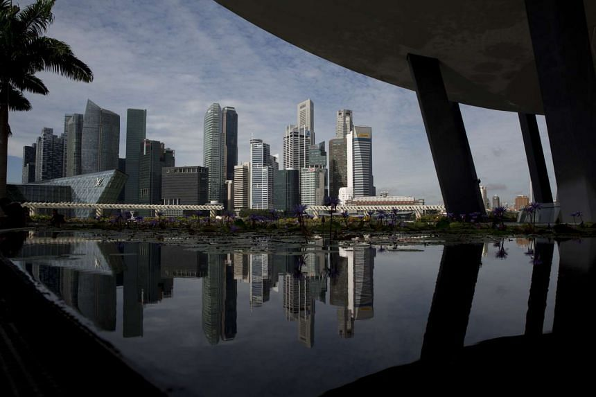 Commercial buildings in the central business district are reflected in a pond at the ArtScience Museum in Singapore, on Dec 9, 2015.
