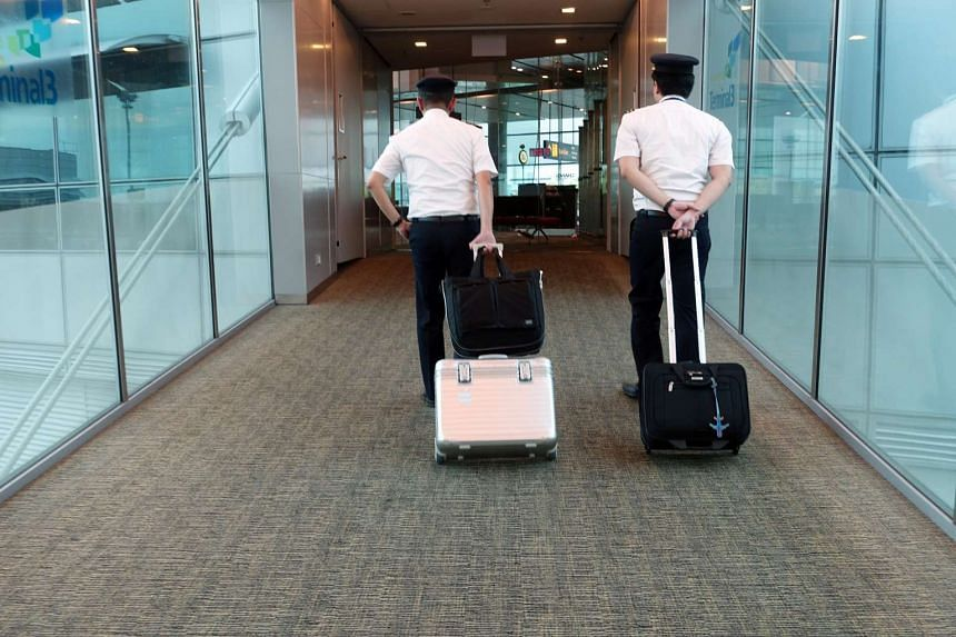 Two Singapore Airlines (SIA) pilots with their luggage at Changi Airport Terminal 3.