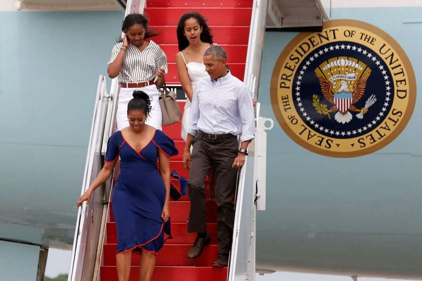 US President Barack Obama (bottom right) and First Lady Michelle Obama (bottom left), arrive with their daughters Malia Obama (top right) and Sasha Obama aboard Air Force One in transit to their annual summer vacation at Martha's Vineyard.