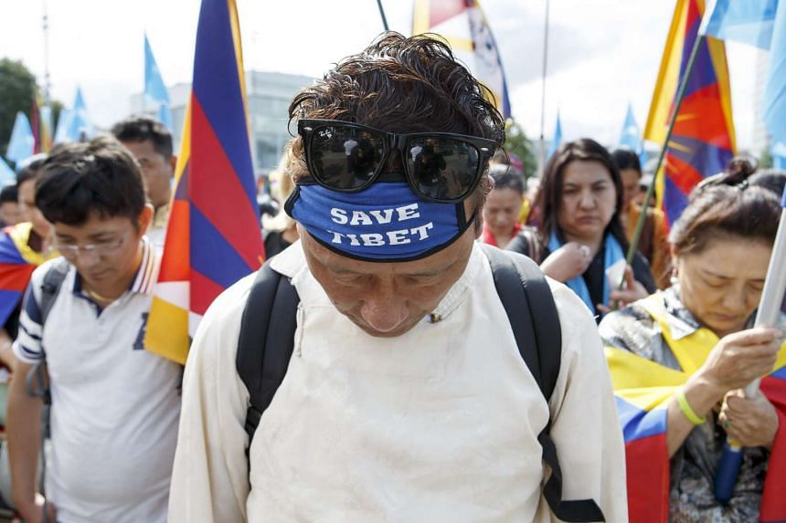 A man with a bandana reading 'Save Tibet' participates in a demonstration on the Place des Nations in front of the European headquarters of the United Nations in Geneva.