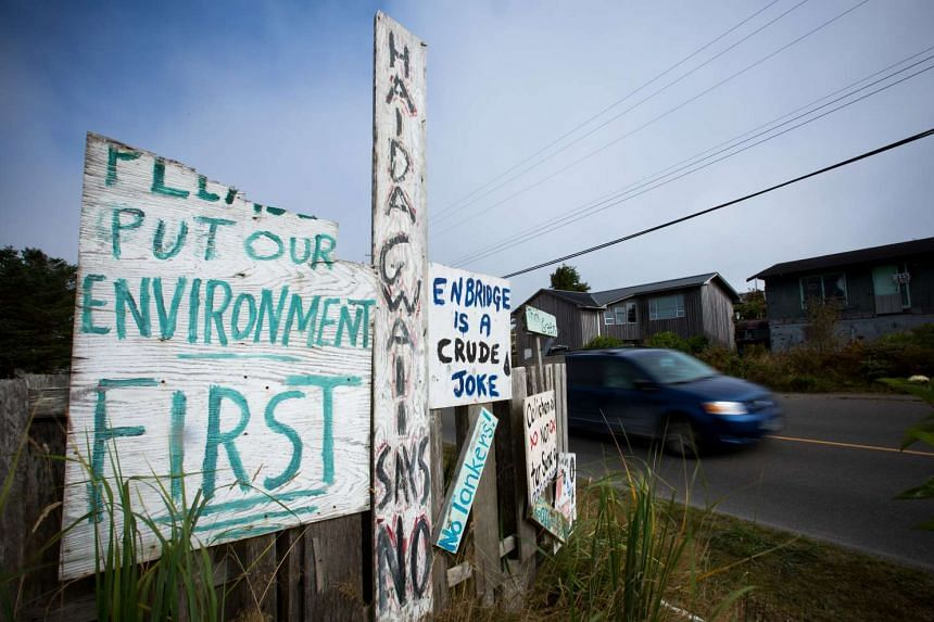 Handmade anti-pipeline signs are seen on the side of a road in the First Nations village of Old Massett, British Columbia, Canada.