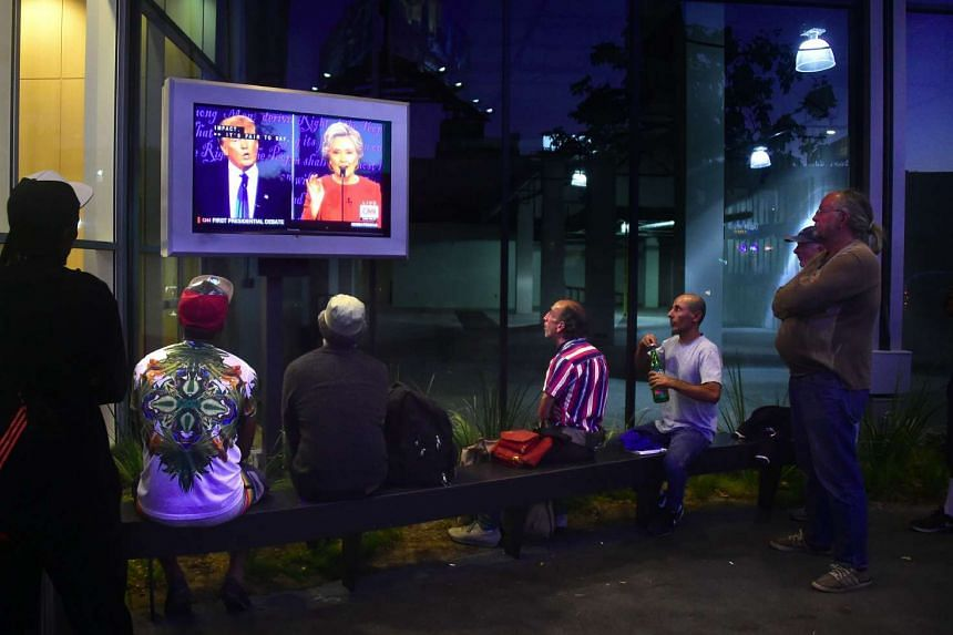 People gather to watch the first US presidential debate between Hillary Clinton and Donald Trump on a television set in front of an office building in Hollywood, California on Sept 26.