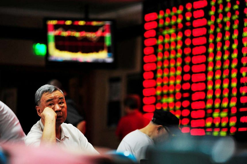 An investor sits in front of an electronic board showing stock information at a brokerage house in Nanjing, China.