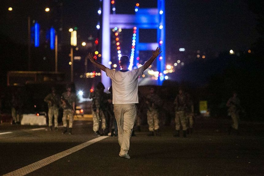 This file photograph taken on July 16, 2016 shows a man approaching Turkish military with his hands up at the entrance to the Bosphorus bridge in Istanbul.