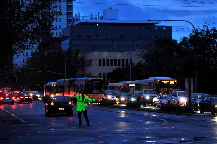 Police direct traffic in the central business district of Adelaide after severe storms and thousands of lightning strikes knocked out power to the entire state of South Australia.