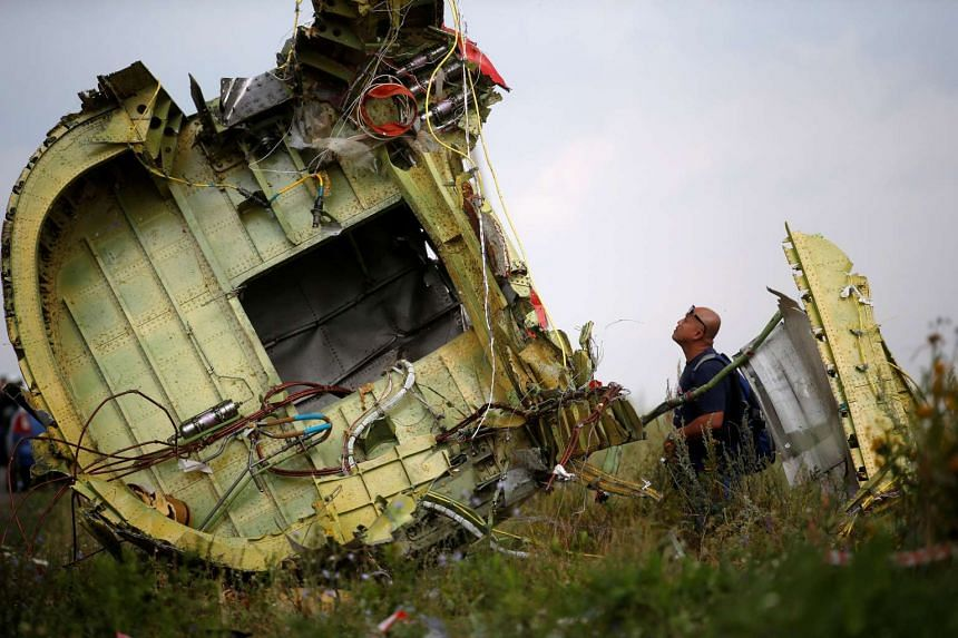 A Malaysian air crash investigator inspects the crash site of Malaysia Airlines Flight MH17 in Ukraine on July 22, 2014.