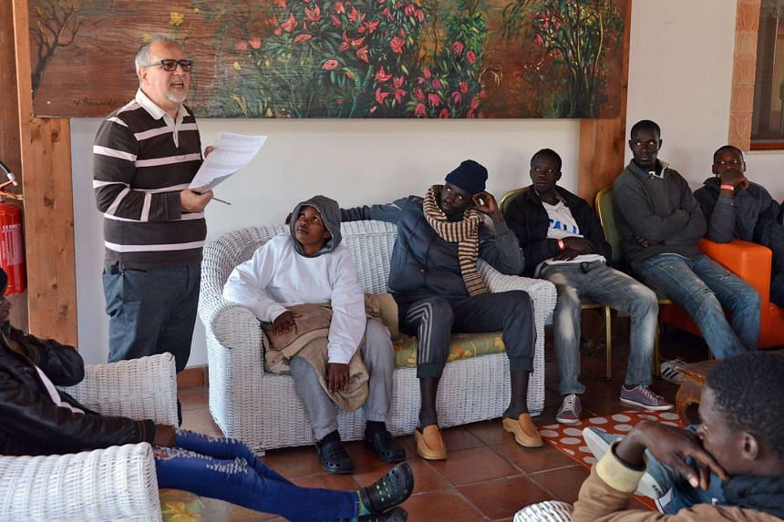 Migrants listening to Francesco Magnano, director of the Oasi Don Bosco immigration centre in Sicily on April 17, 2015.
