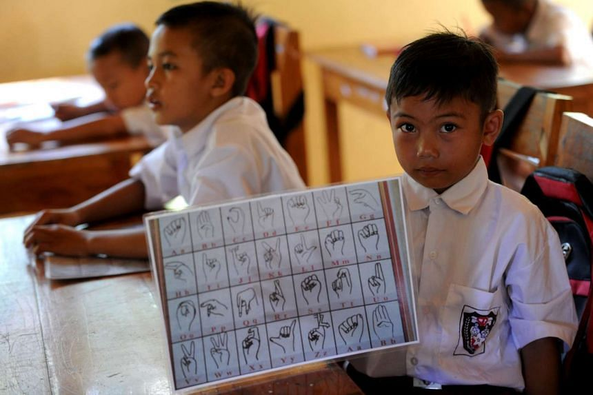 A schoolboy holding paper signs for learning at an elementary school at the Bengkala village in Bali.