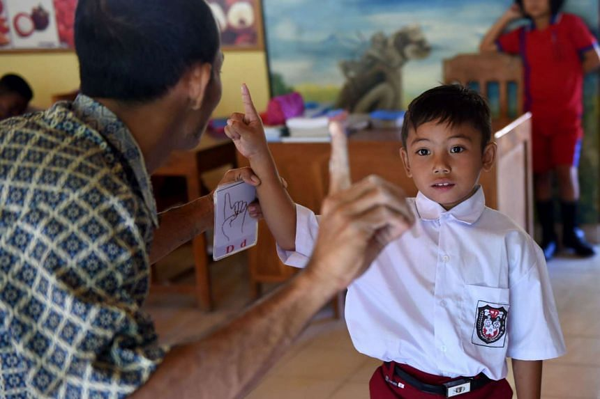 A teacher speaking with sign language to a deaf schoolboy at an elementary school at the Bengkala village in Bali.