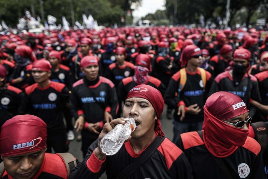An Indonesian laborer drinks water as they march toward the presidential palace during a rally in Jakarta, Indonesia on Sept 29, 2016.