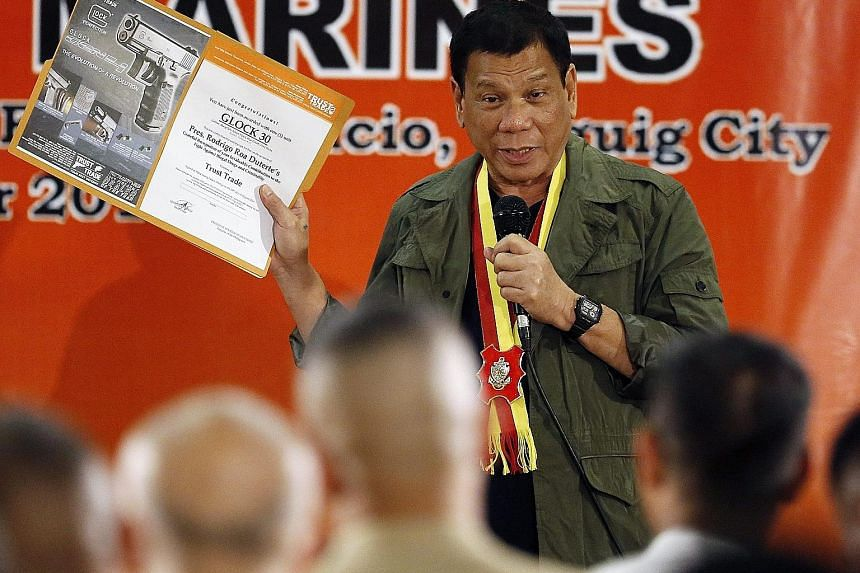 President Duterte with a picture of a Glock 30 pistol during his visit to the HQ of the Philippine Marines on Tuesday. Since taking office five months ago, he has given almost half his public speeches to a military audience - far more than his predec