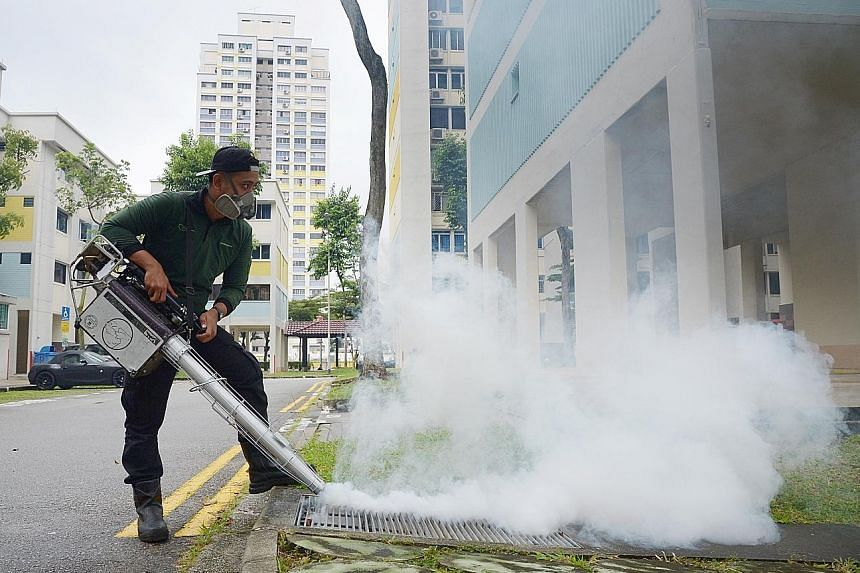 A contractor engaged by the town council fumigating the precinct of Bishan earlier this month.