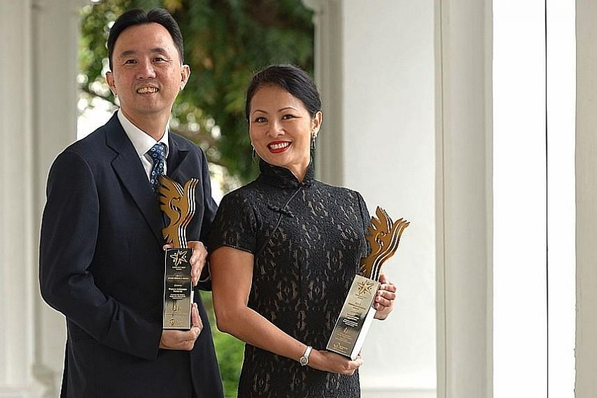 ST Kinetics' Mr Cheng and UOB's Ms Rappa with their companies' Pinnacle Awards at the Istana yesterday. The award is the highest given to organisations or individuals who have supported the Community Chest.