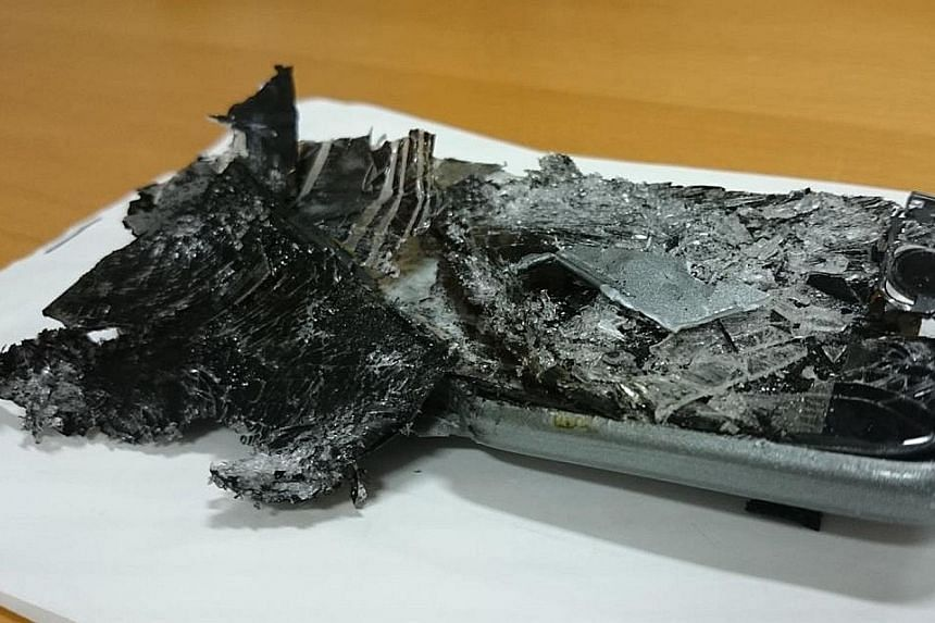The charred remains of an unidentified cellphone which caught fire during a Qantas flight in June.