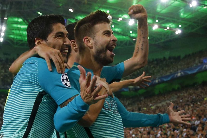 Barcelona's defender Gerard Pique (right) celebrates scoring the 1-2 goal with his teammates.