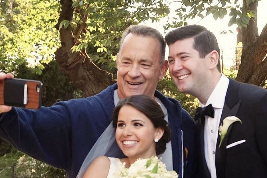 Actor Tom Hanks taking a selfie with a couple who were having a wedding photo shoot in Central Park.