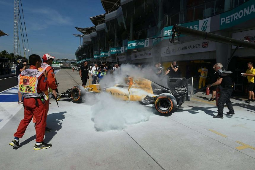 Renault driver Kevin Magnussen's car is engulfed in flames at the pit during the first free practice session of the Formula One Malaysia Grand Prix in Sepang on Sept 30, 2016.