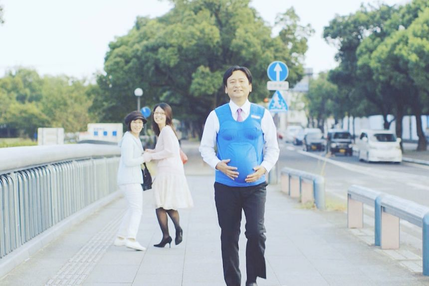 Saga Prefecture governor Yoshinori Yamaguchi wears a vest that recreate a woman's breasts and belly at seven months of pregnancy in this handout screen grab.