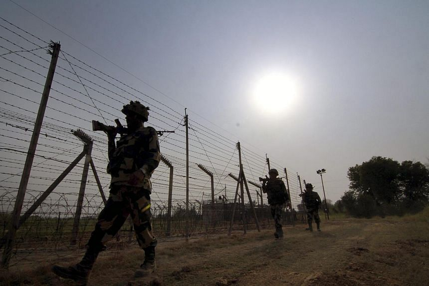 Members of the Indian Border Security Force patrolling near the fence at the India-Pakistan International Border at the Budwar post of the Arnia sector in May 2016.