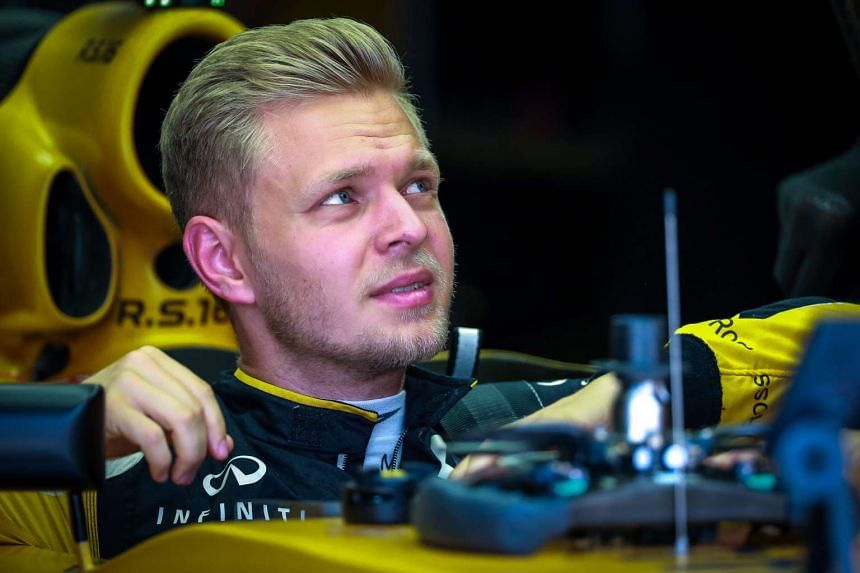 Kevin Magnussen of Renault sits in his car as team mechanics do work after it caught fire during the first practice session for the Formula One Grand Prix in Sepang, Malaysia on Sept 30, 2016.