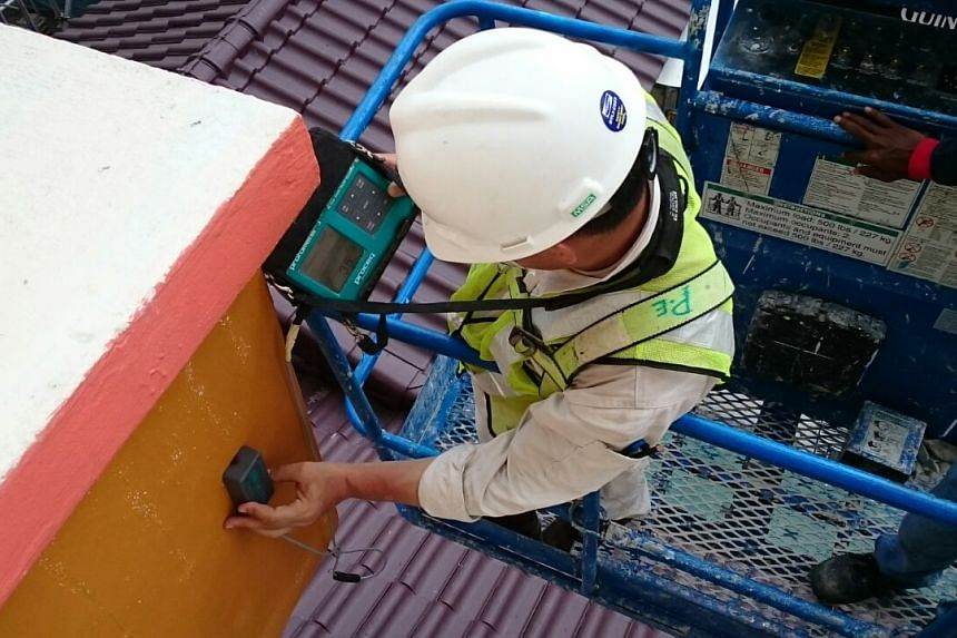 A tester deploying ultrasound scanning to check on all sunshades in Block 201E, Tampines Street 23, on Sept 30, 2016.