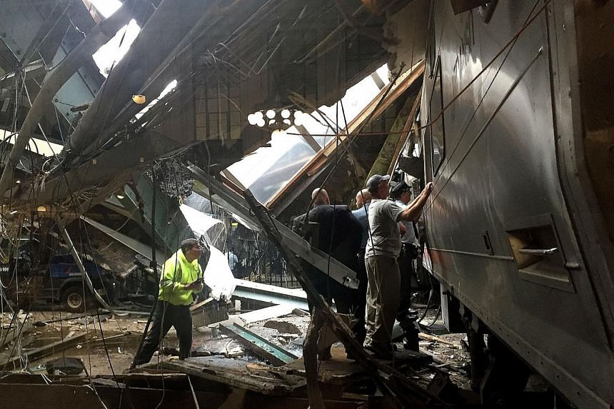 Train personnel inspecting a New Jersey Transit train that crashed into the platform at the Hoboken Terminal yesterday during morning rush hour, killing at least three people and injuring more than 100 others. A witness said the train hit a cement bl