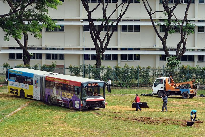 Once dislodged, the bus was hauled to the entrance of the field and later towed away. Above: The bus stuck deep in soft ground up to its bumper. Left: It was eventually pulled out by a tow truck after futile attempts earlier to level the bus so it co