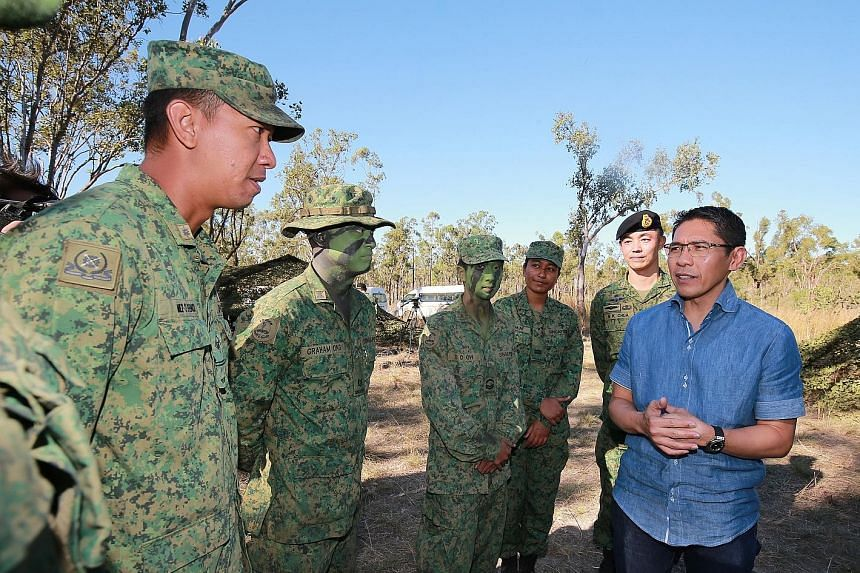 Dr Maliki (in blue shirt) with soldiers, including ME2 Muhammad Efendi Ismail (extreme left), at Exercise Wallaby in Australia on Wednesday. Behind him is exercise director, BG Chua Boon Keat (wearing beret).