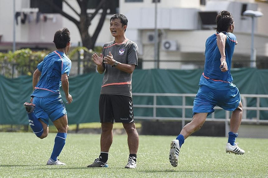 Albirex Niigata coach Naoki Naruo (centre) conducting training at the Jurong East Stadium. His eye for detail has been cited as a reason why Albirex are on the brink of completing an unprecedented treble this season.