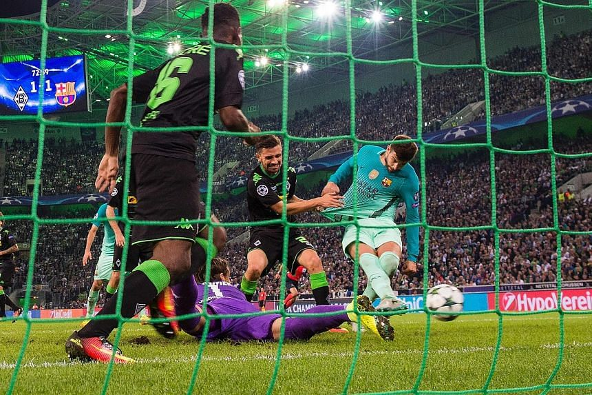 Barcelona defender Gerard Pique (right) scores the winner from close range after Monchengladbach goalkeeper Yann Sommer (in purple) fails to clear the ball to safety following a shot by Luis Suarez.