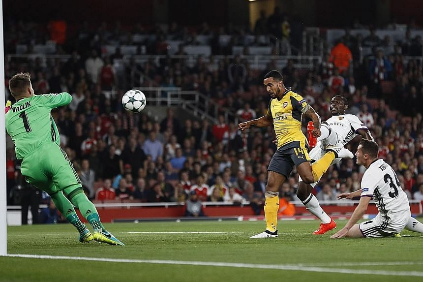Top: Arsenal forward Theo Walcott scoring the opener against FC Basel in the seventh minute on Wednesday. He added a second 19 minutes later. Above: Basel's 25-year-old midfielder Taulant Xhaka (right) swops shirts with his brother Granit Xhaka, 24,