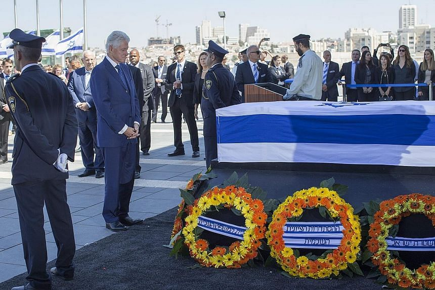 Former US president Bill Clinton standing before the coffin of Mr Shimon Peres yesterday. The former Israeli president's death on Wednesday at the age of 93 triggered an outpouring of grief and tributes that hailed his transformation from hawk to fer