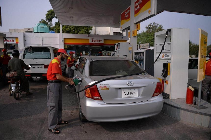 Pakistani attendants fill vehicles at a gasoline station in Islamabad on Sept 29, 2016.