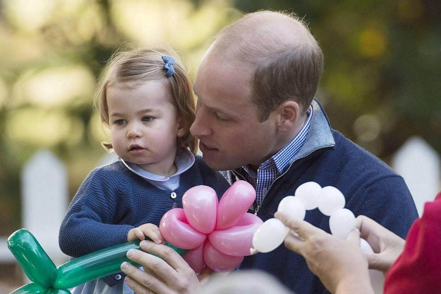 The Duke of Cambridge holds his daughter Princess Charlotte during a children's party at Government House in Victoria, British Columbia, Canada on Sept 29, 2016.