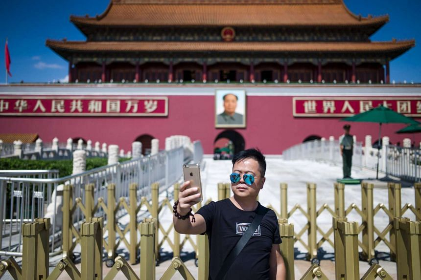 A tourist takes a selfie in front of a giant portrait of Mao Zedong at the gate of the Forbidden City in Beijing on Sept 6, 2016.